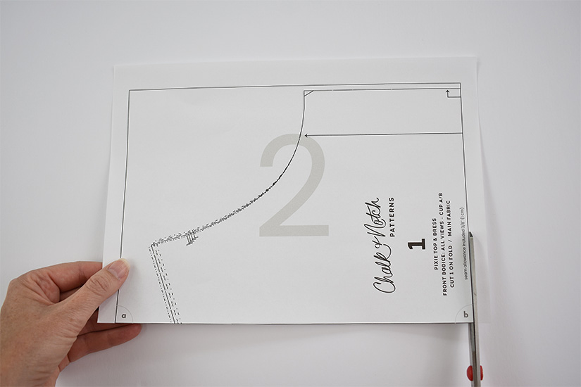 Scissors cut the right side of a border on a pdf sewing pattern page.
