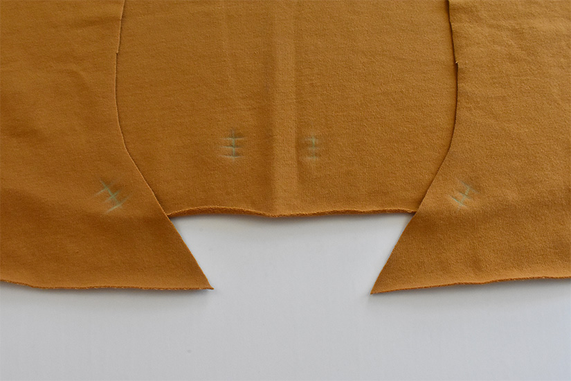 Golden color fabric pieces are shown with chalk markings indicating buttonhole/grommet placement.