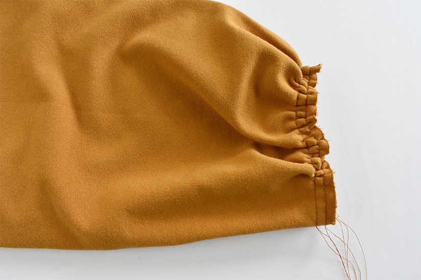 Basting stitches are pulled to gather the opening of a gold colored sleeve.