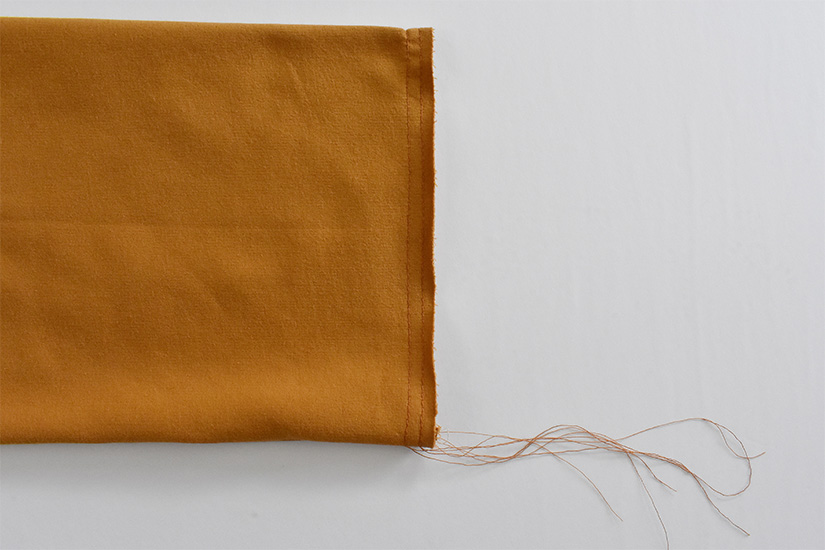 Basting stitches are shown on the end of a sleeve.