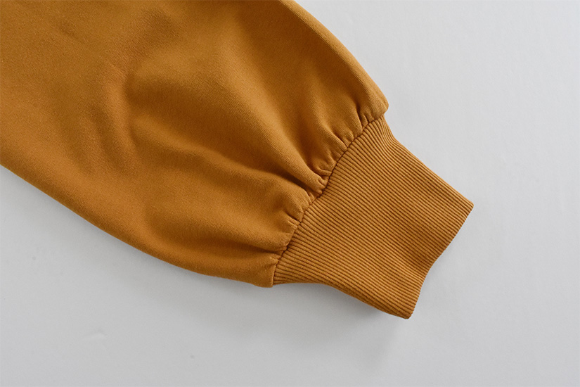 A close up of a gold colored gathered sleeve and cuff.