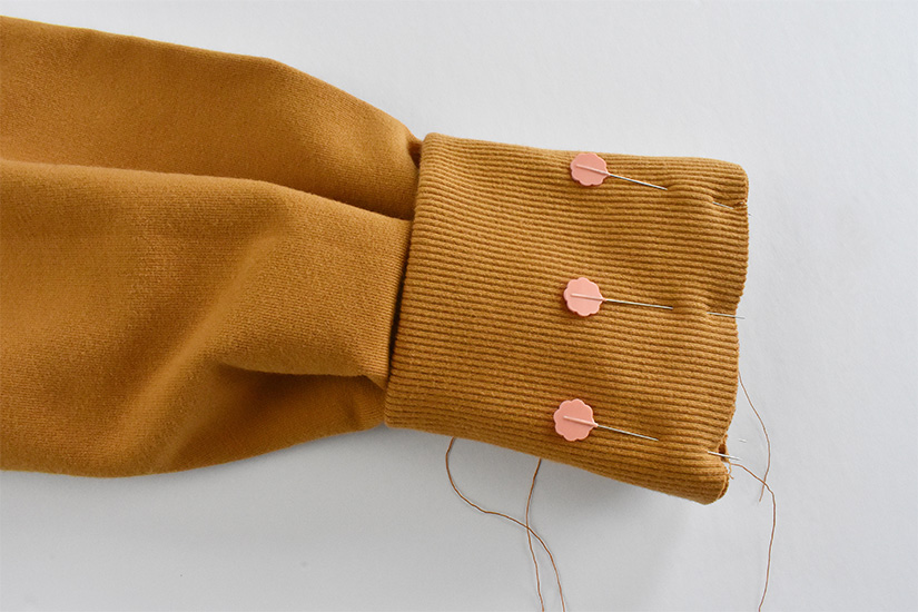 A rib knit cuff is shown pinned to the end of a sleeve.