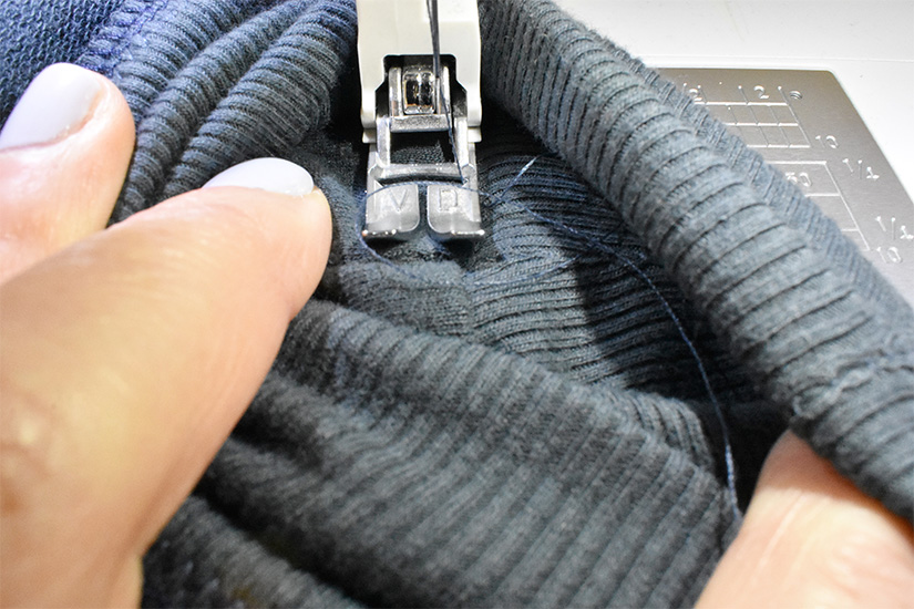 A sewing machine foot is shown sewing on dark blue/green fabric