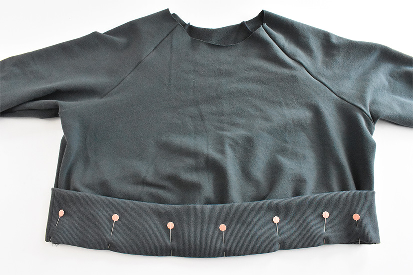 Rib knit hem band in blue/green fabric is shown pinned to bottom of hoodie bodice.