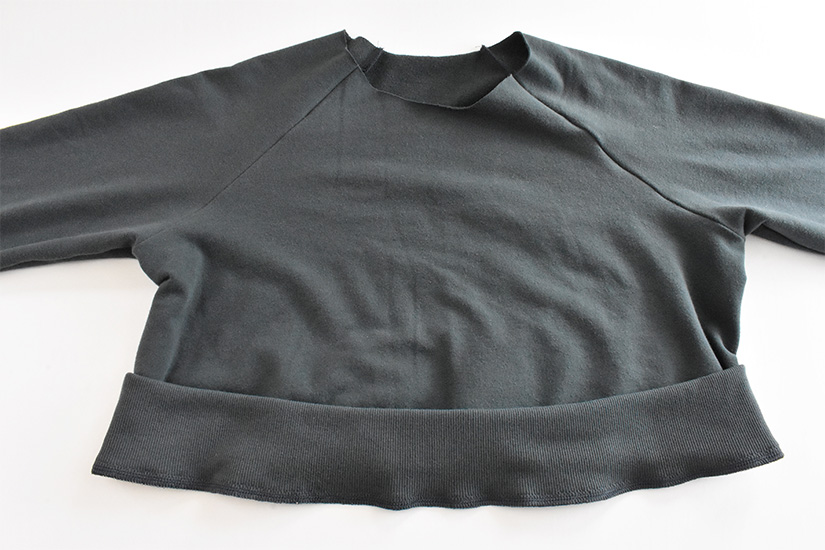 Rib knit hem band in blue/green fabric is shown sewn to bottom of hoodie bodice.