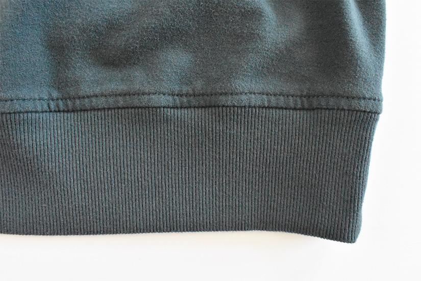 Close up of topstitching on blue/green fabric hem band.