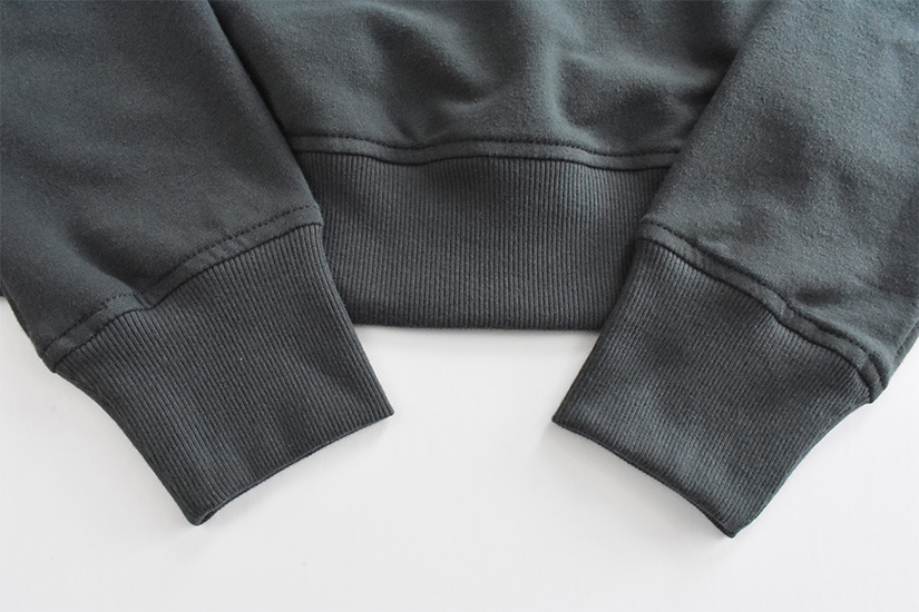 Close up of topstitching on blue/green fabric hem bands and cuffs