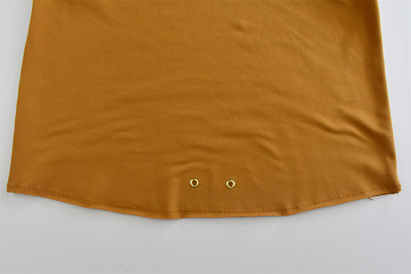 A close up of stitching on the bottom of a gold hoodie bodice