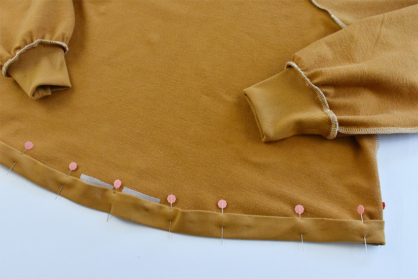 """The hem of a gold colored hoodie is shown pinned and pressed to the wrong side by 1"""""""