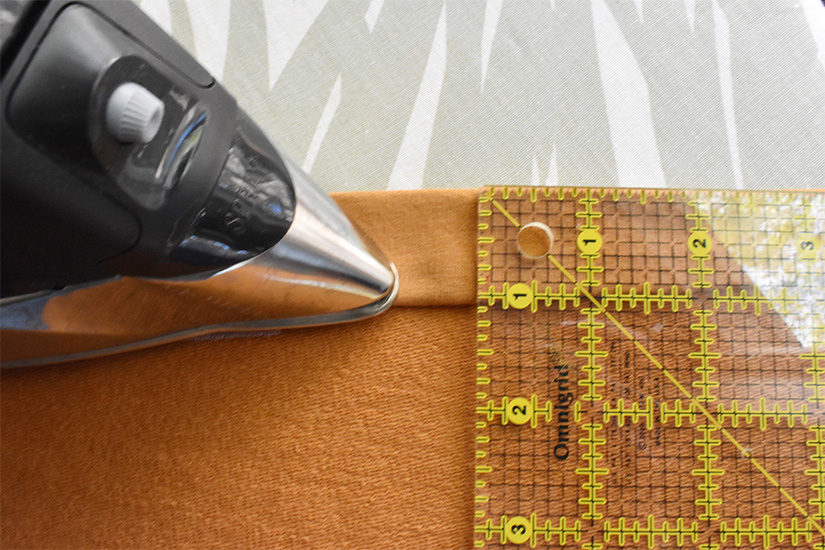 """An iron and ruler are shown pressing golden yellow fabric to the wrong side by 1"""""""