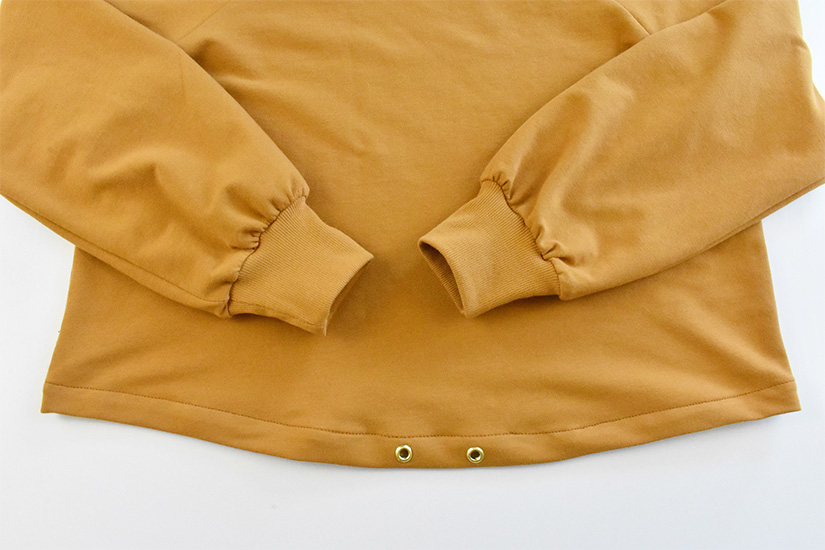 The hem on a gold colored hoodie is shown sewn.