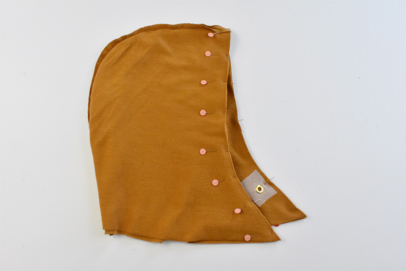 Gold colored hood and lining pieces are shown pinned together at the front opening.