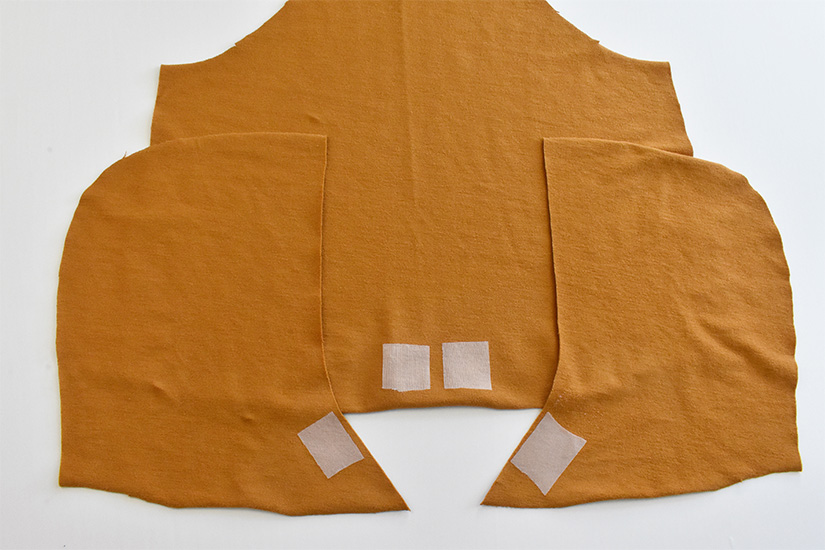 Small squares of fusible interfacing are shown fused to gold colored fabric pieces for the front bodice and hood of the Page Hoodie