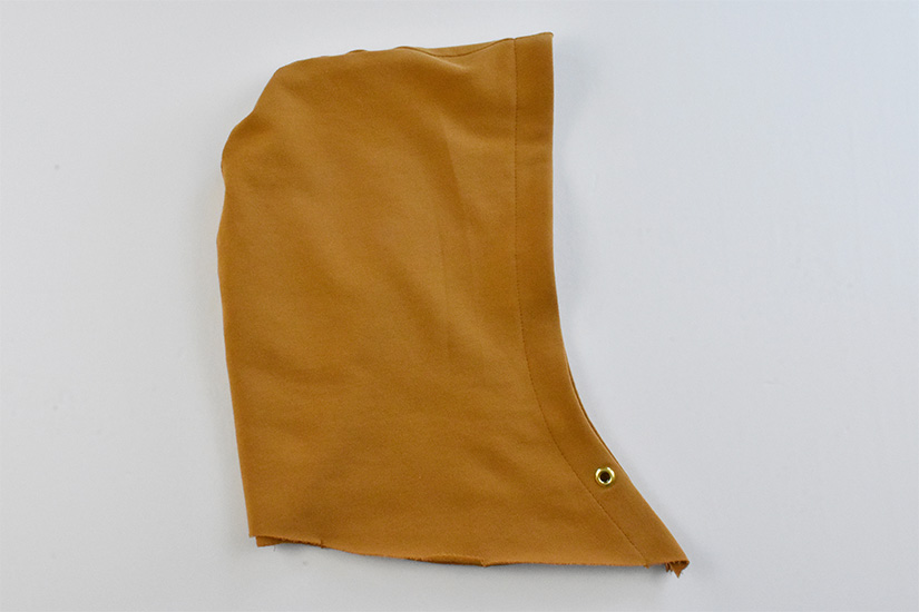 A sewn hood piece in gold colored fabric