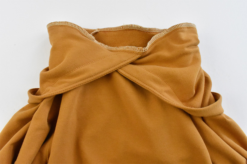 The neckline of a gold hoodie is shown with the hood sewn to it.
