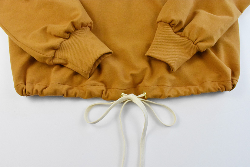 A close up of the drawstring hem on a gold colored hoodie
