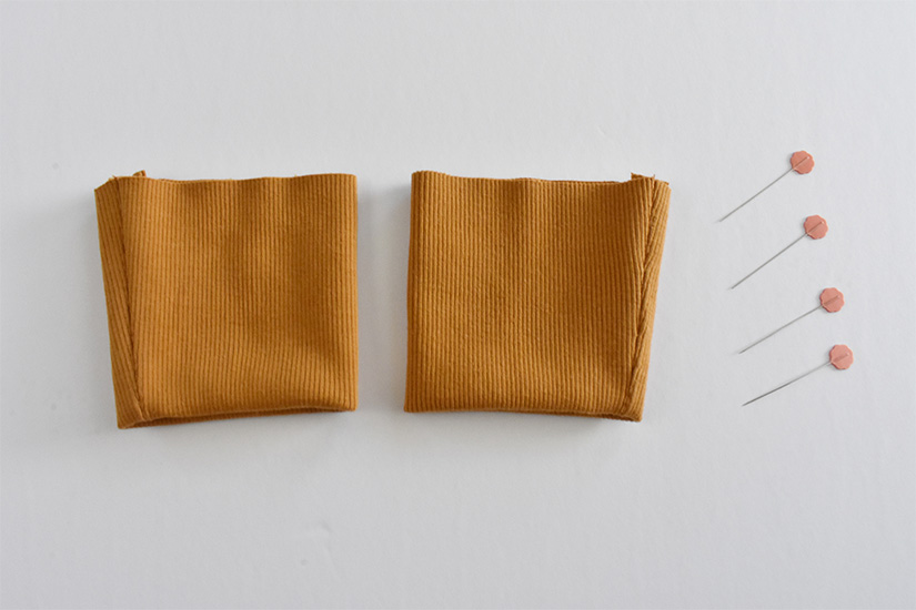 Gold colored rip knit fabric is folded into cuffs.