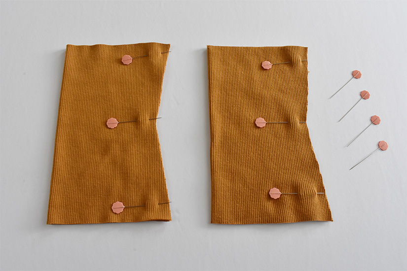 Gold colored rib knit tubes are pinned on the right side.