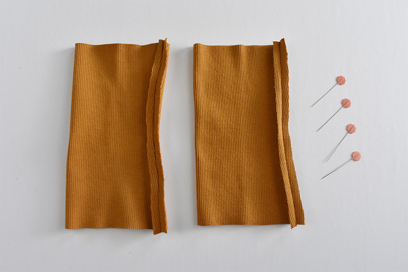 Gold colored rib knit fabric tubes are sewn with the seams pressed open.