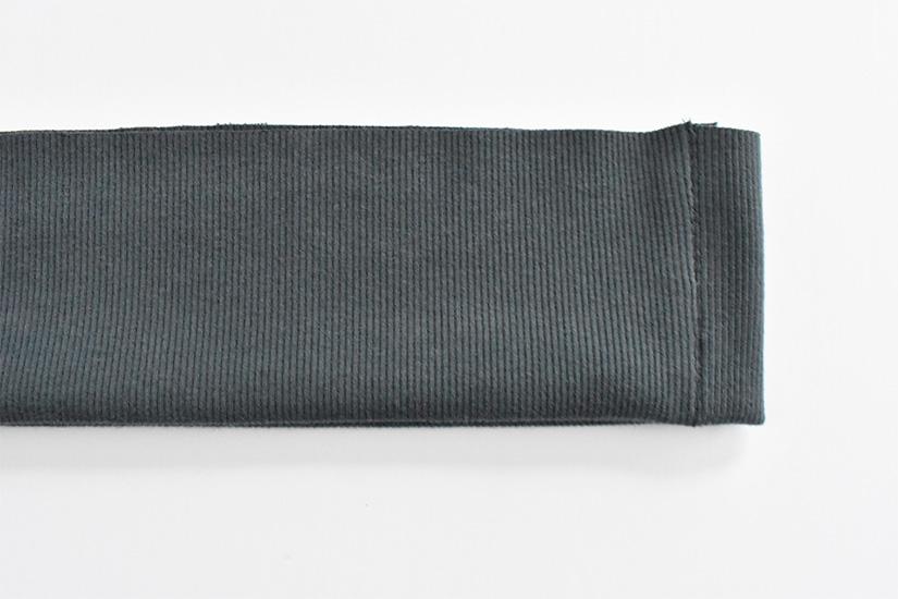 A dark blue/green rib knit hem band is shown folded in half