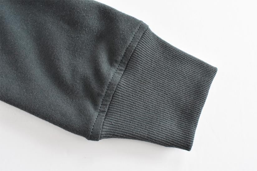 Close up of topstitching on a dark blue/green sleeve cuff