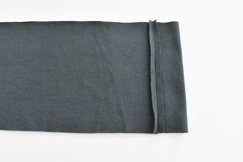 A seam on dark blue/green rib knit fabric is pressed open.