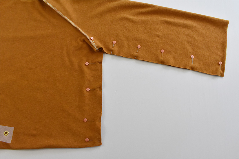 The inside bodice of a gold colored hoodie is shown with the bodice and side seams pinned.