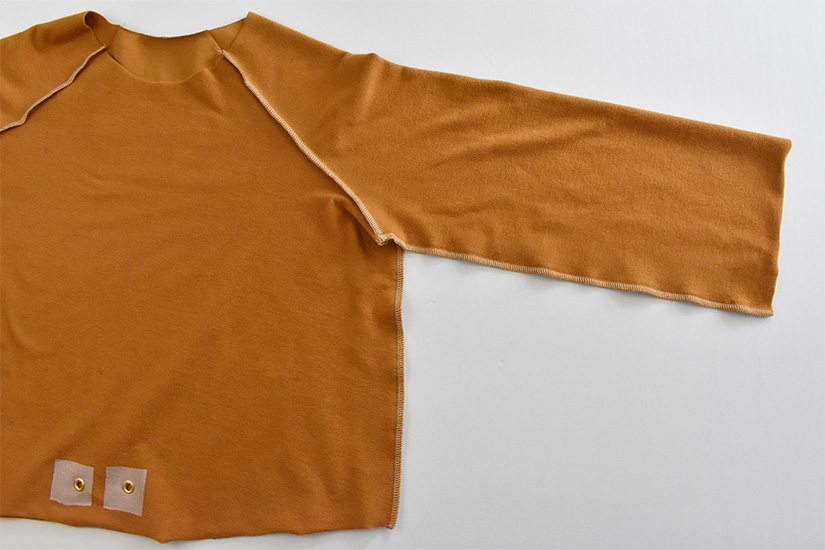 The inside bodice of a gold colored hoodie is shown with the bodice and side seams sewn.