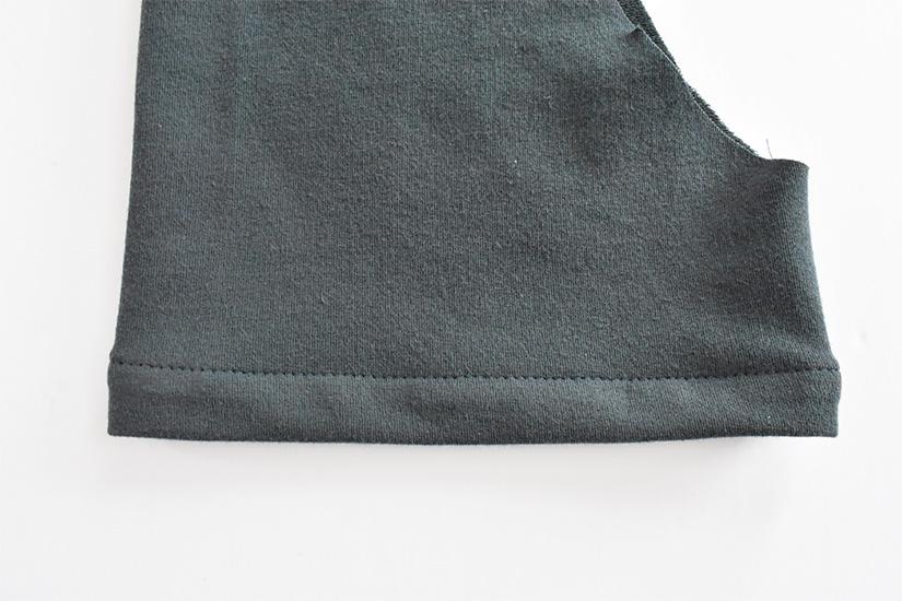 the hem of a short sleeve on blue/green fabric.