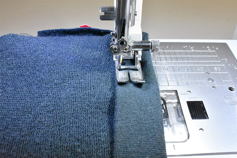 A sewing machine foot stitches on the folded edge of blue/green fabric