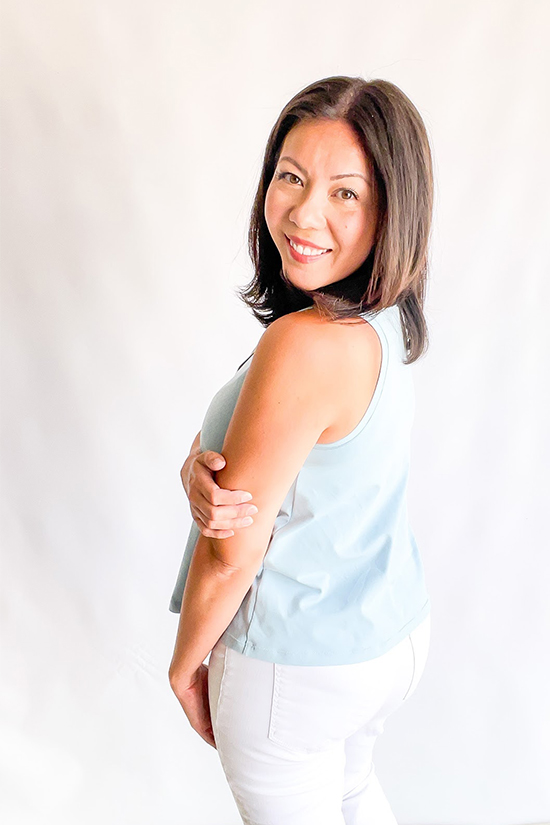 Michele stands with her side to the camera. She's wearing a light blue tank top and white jeans.