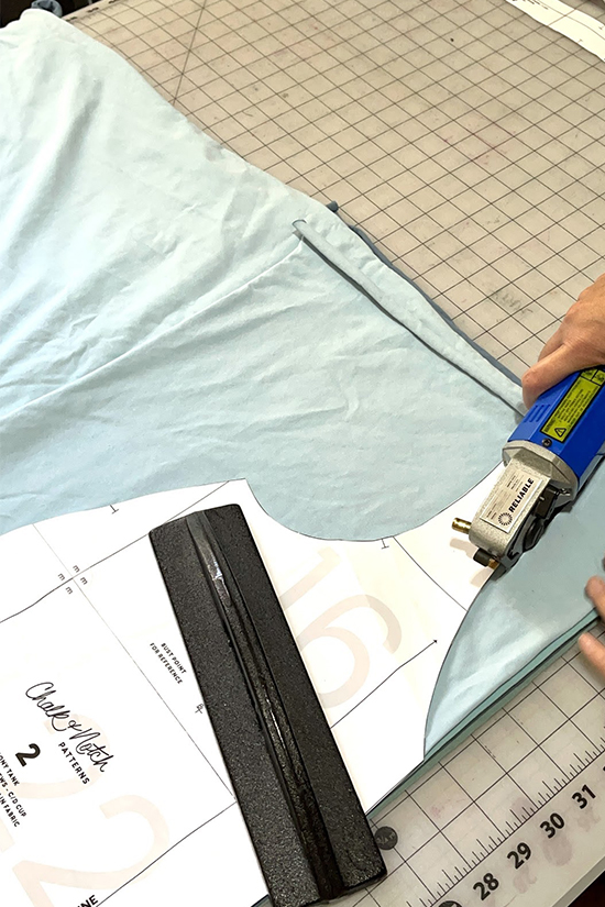 An electric rotary cutter cuts through several layers of fabric.