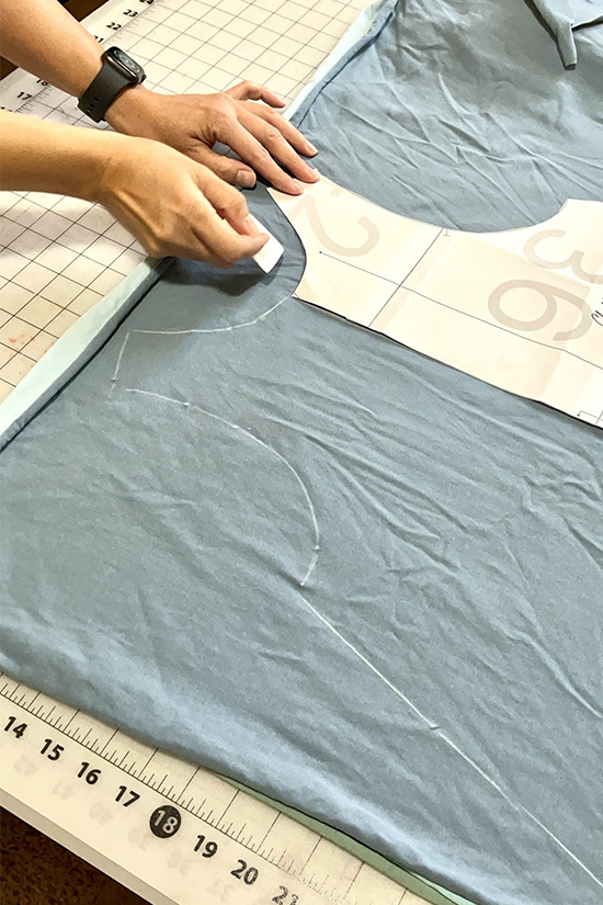 A pattern and a chalk outline are shown on blue fabric