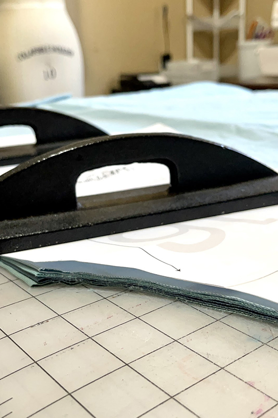 A heavy pattern weight sits on four blue fabrics.