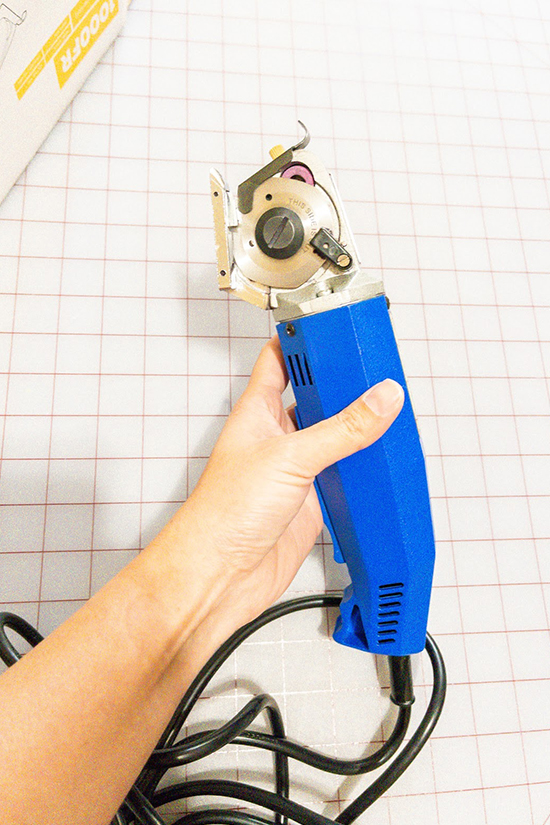 A hand holds an electric rotary cutter.