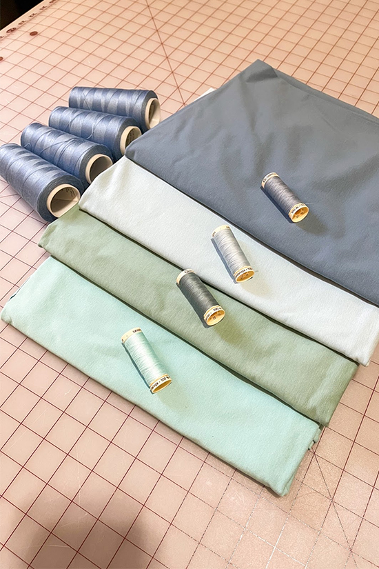 Four blue colored fabrics are shown laying on a cutting mat.