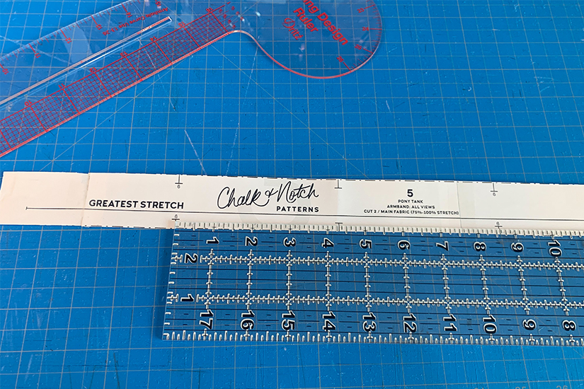 A ruler and armband pattern piece lays on a blue cutting mat.