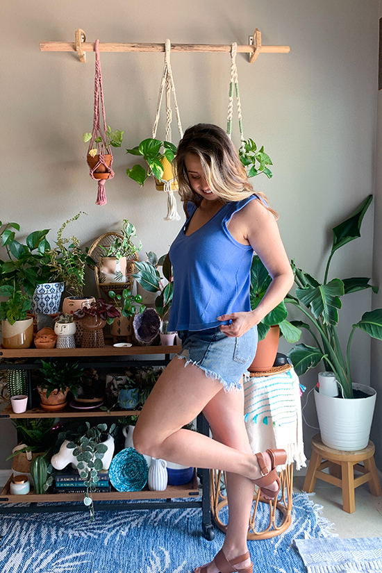 Olivia stands wearing brown sandals, jean shorts and a blue ruffle armband tank top.