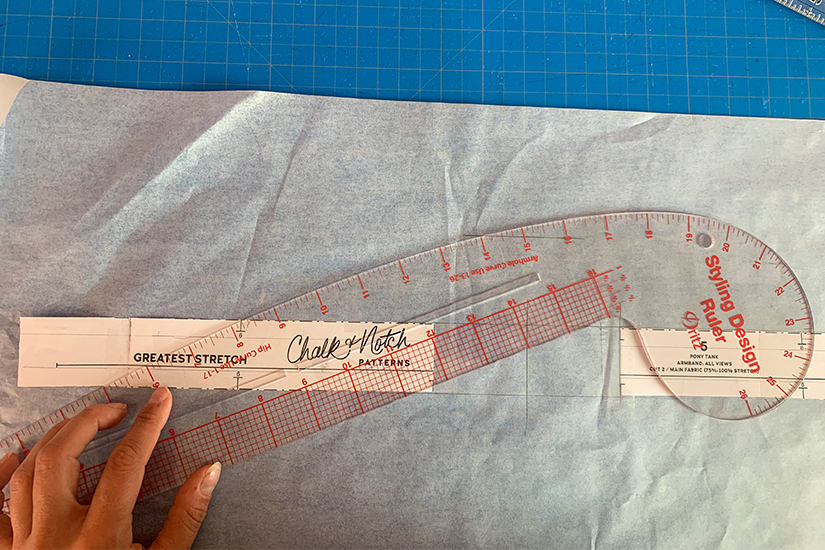 A curve ruler is shown on an armband pattern piece and tracing paper.