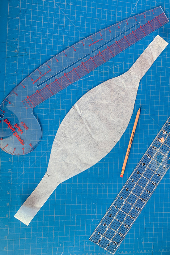 The newly traced ruffle band pattern piece is shown on a blue cutting mat.