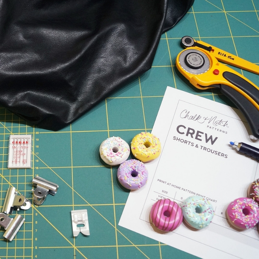 Black faux leather and various sewing tools on a green cutting mat.