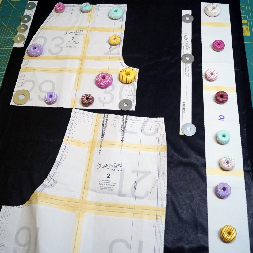 paper pattern pieces are laid out on black faux leather with pattern weights laying on top