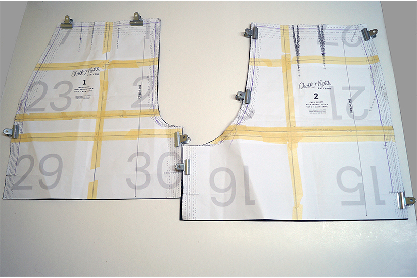 paper pattern pieces are clipped to faux leather.