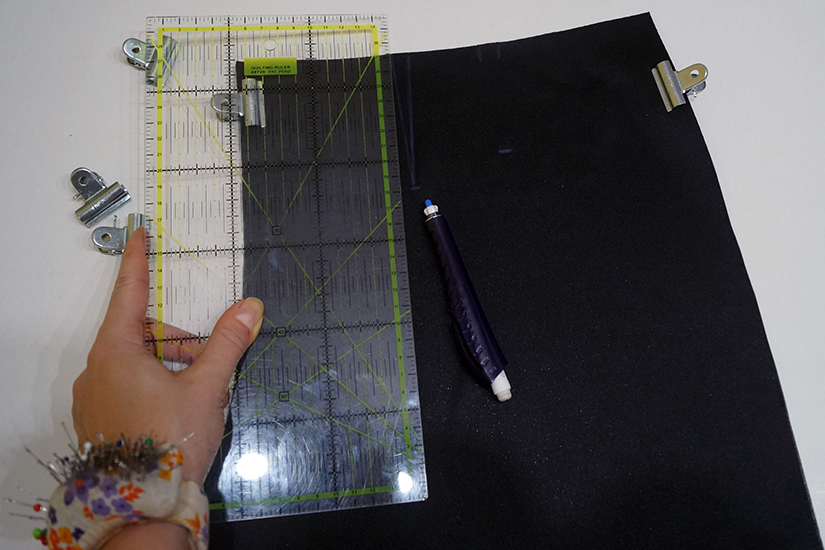 A ruler and clips lay on a faux leather pattern piece