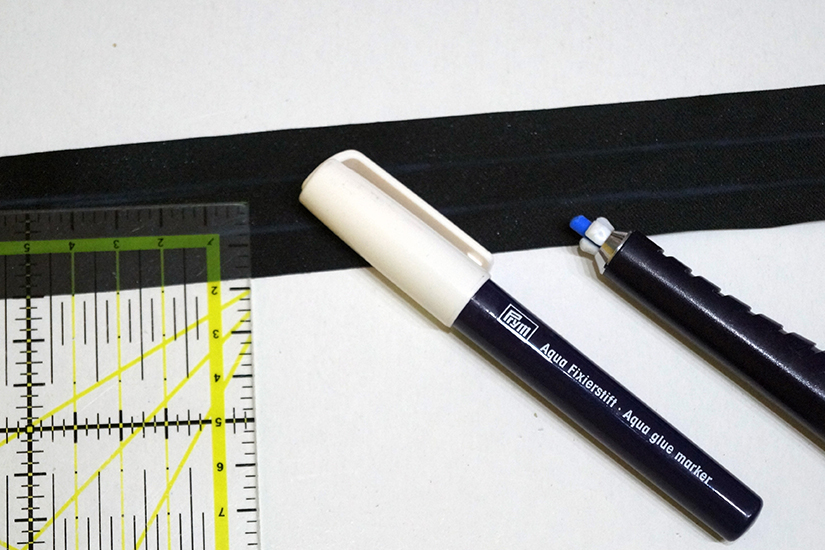 A ruler, strip of faux leather, and chalk marker lay on white background.